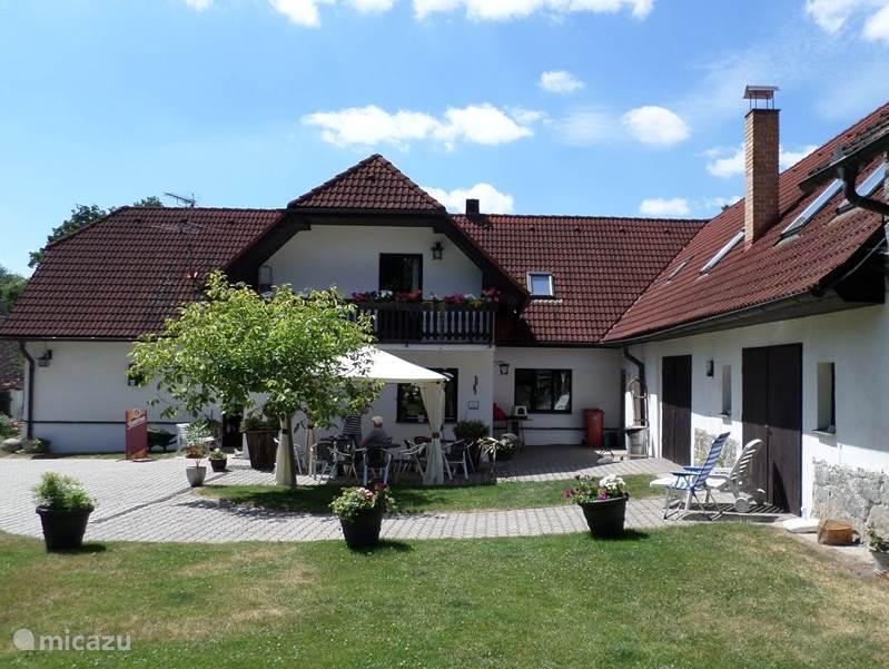 Aan de rechterzijde de appartementen met de mooie voortuin inclusief een terras en gezellige zitjes.