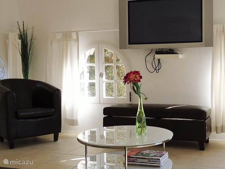 Woonkamer met grote TV, fauteuils en (slaap)bank