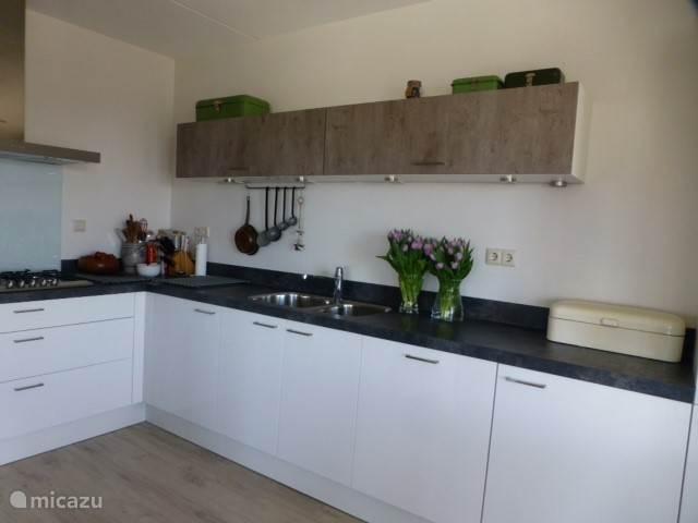 Keuken met vaatwasser, koelkast en oven/magnetron.