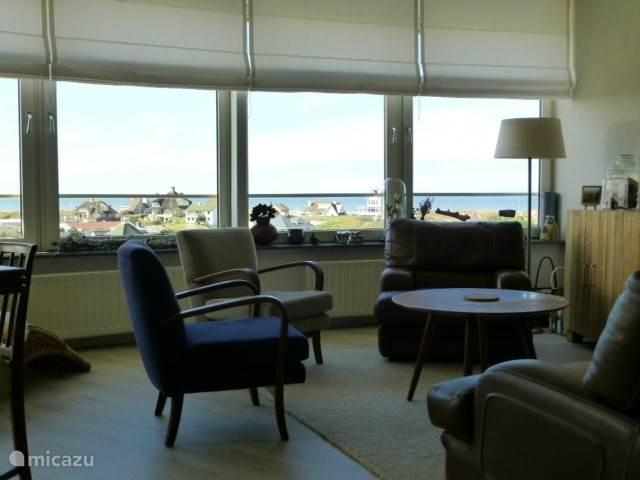 Vanuit deze zithoek een wijds zicht op de luxe villa's op de duinrand en de Noordzee.