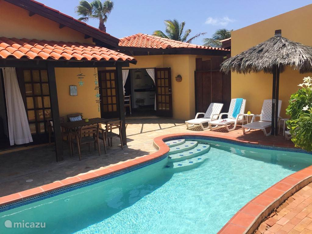 In the shade of the palapa, you can relax by the pool.