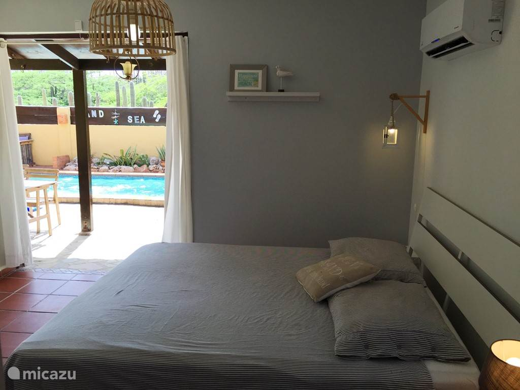 The master bedroom with double doors open to the pool area.