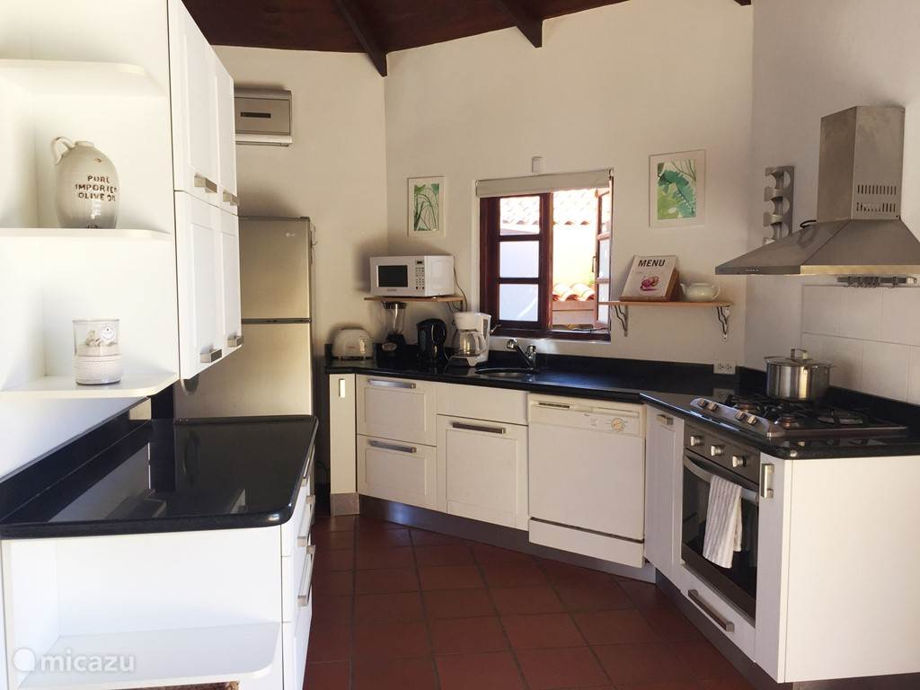 Modern, fully equipped kitchen with a 4-pits cooktop, oven, microwave, dishwasher and large fridge.