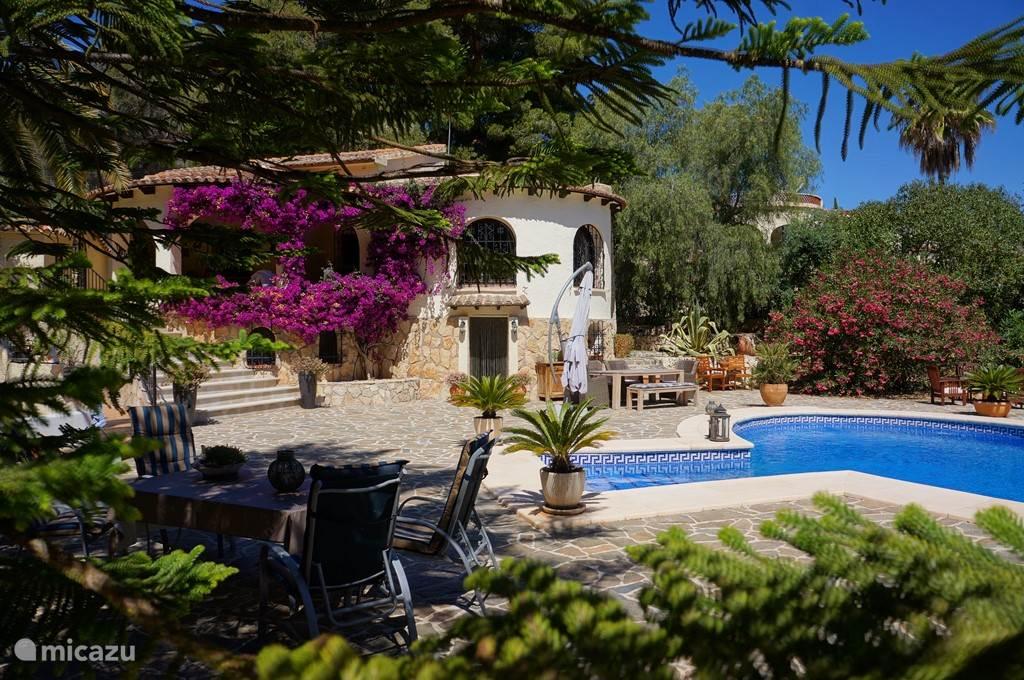 Uitzicht op het huis en zwembad vanaf een schaduwrijke plek. Schaduw is zeer aangenaam in de zomer.