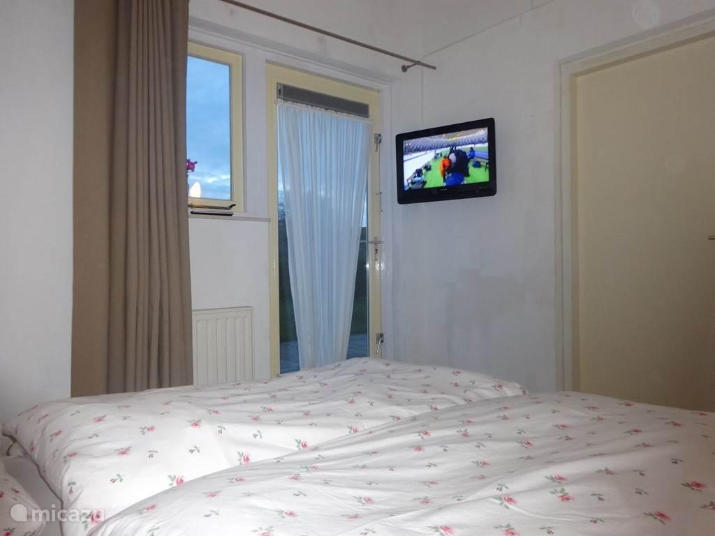 Tweepersoonskamer op de begane grond met TV en badkamer.