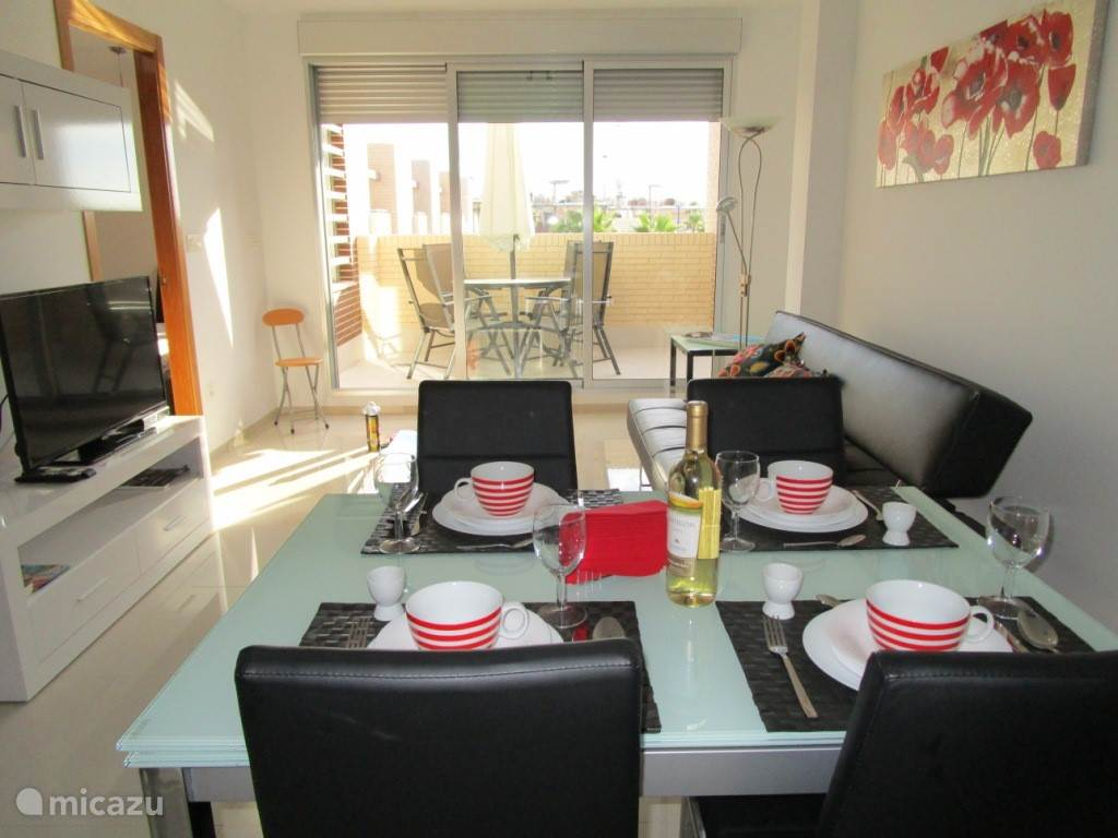 Dit is de nieuwe ruime woonkamer met balkon. Het appartement beschikt over gratis WiFi, NL TV en airconditioning warm/koud. Het balkon is een heerlijke plek om te ontbijten. De Spaanse zon schijnt hier vanaf zonsopkomst tot in de middag.