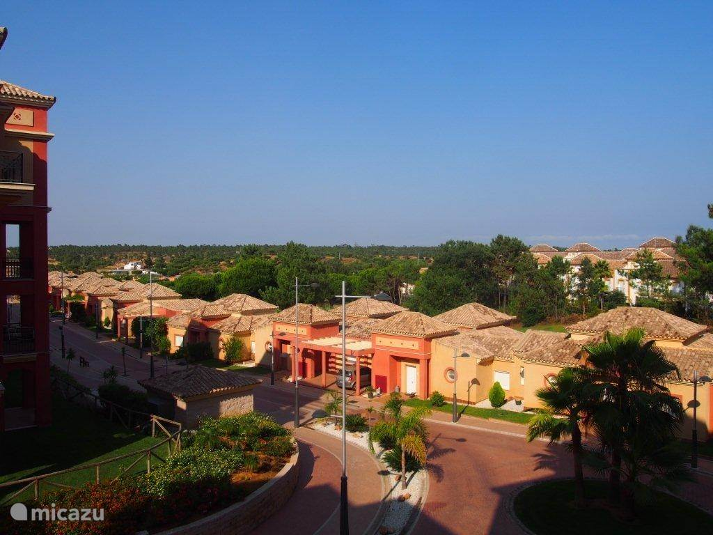 Uitzicht vanaf het balkon naar rechts (aan de rechterkant van de lage bungalows ligt een hole van de golfbaan)