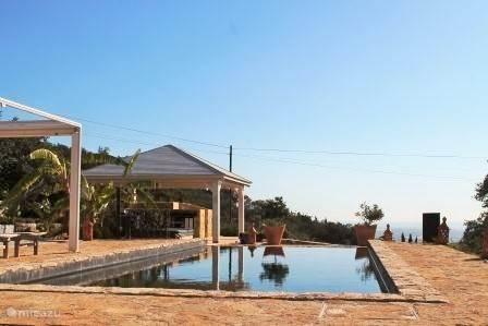 Het zwembad met buitenkeuken en zonneterras.