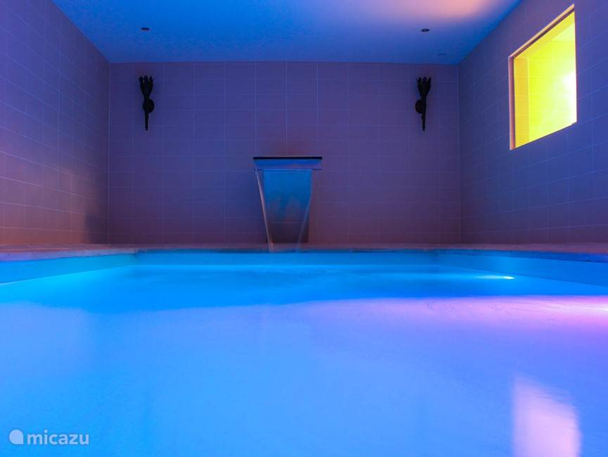 Luxe verwarmd binnenzwembad met verlichting en waterval