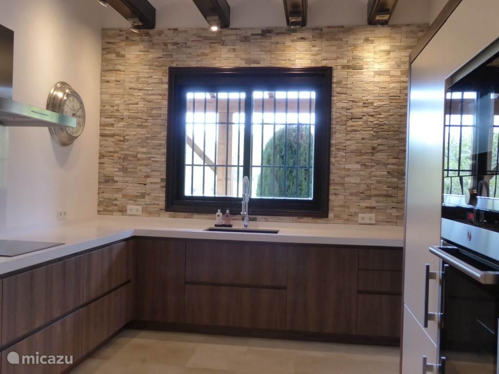 Moderne keuken met inbouwmagnetron, hete luchtoven, koelkast, vriezer, vaatwasser, elektrische kookplaat en Nespresso-koffiemachine