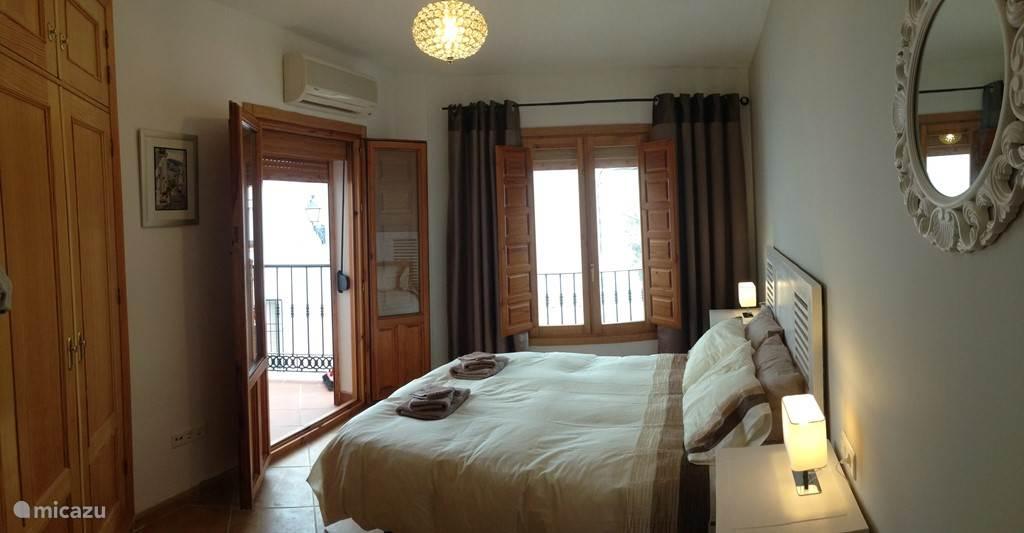 slaapkamer met 2 persoon bed en openslaande deuren naar terras.