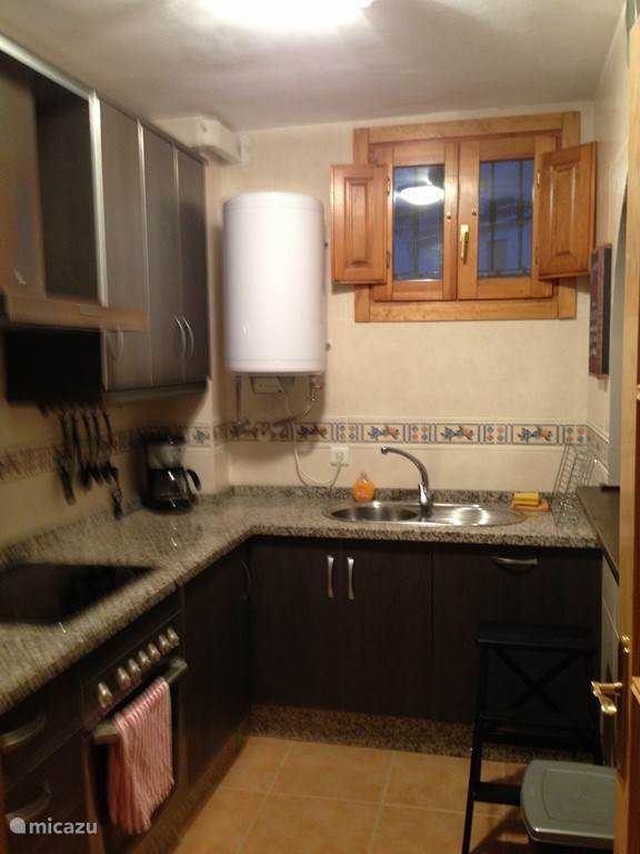 compleet ingerichte keuken met oven, koelkast, vriezer, keramische kookplaat, afwasmachine en wasmachine.