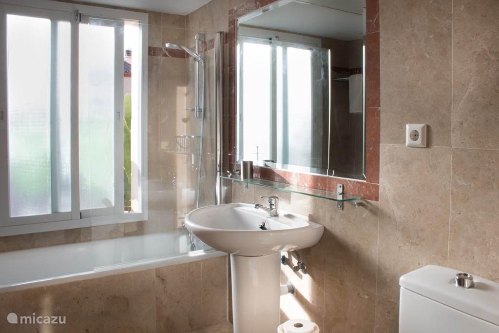 2e badkamer in huis; met ligbad, douche met glazen spatwand, toilet en wastafel.