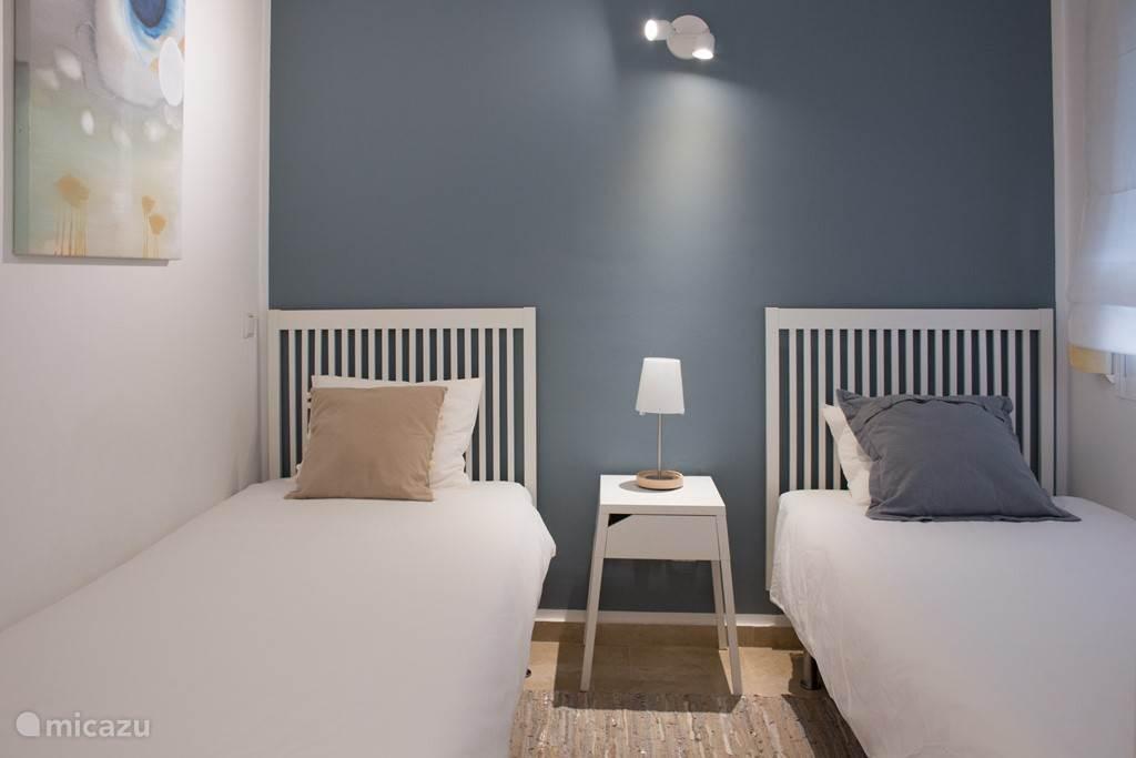 De blauwe kamer! 2 eenpersoonsbedden maat 90x200. Kamer in rustige wit, zand-, en blauwtinten. Met groot raam en grote kledingkast.