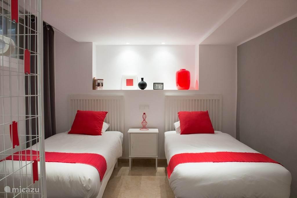 In grafische kleuren wit, donkergrijs en frisrood. Deze kamer ligt op souterrain niveau.