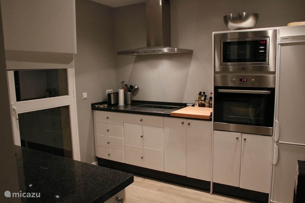 De keuken is van alle gemakken voorzien, met oven, magnetron, waterkoker, broodrooster, Nespresso en filterkoffie apparaat, een tosti apparaat, vaatwasser en  ruime keuze aan serviesgoed. Met deur naar tuin met eettafel