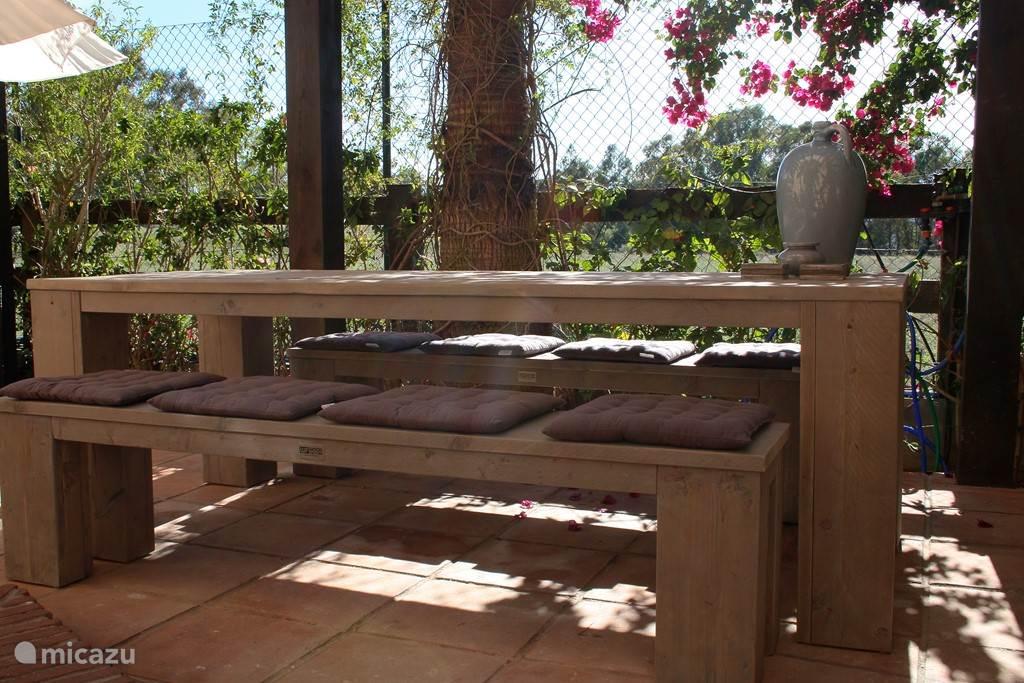 De tuintafel, een heerlijke plek om te ontbijten of om 's middags in het zonnetje te zitten.  Met gefilterd licht door de palmbomen en vrij uitzicht op de velden biedt de tuin veel privacy.