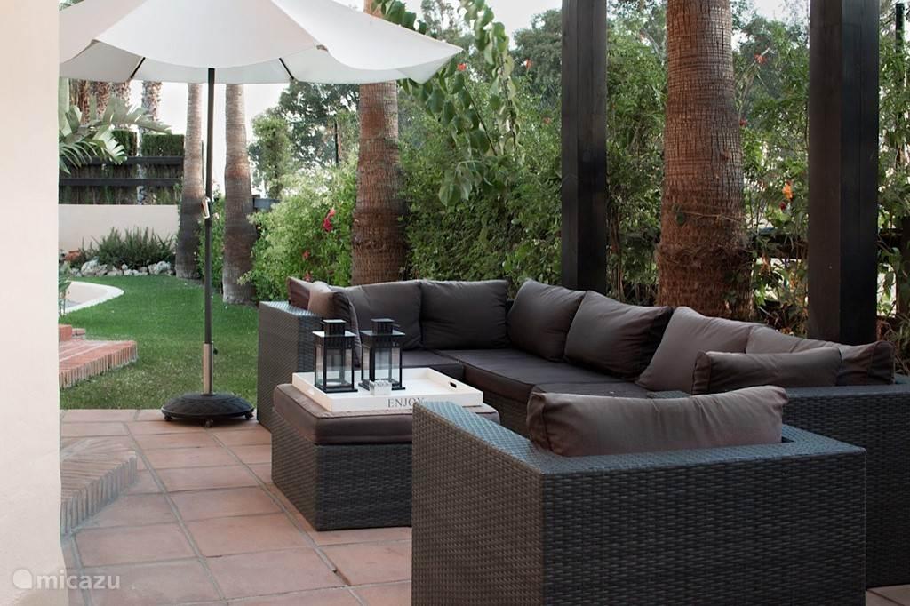 De loungehoek met een stuk gazon. Via de tuin is het ook makkelijk om de (stille) straat over te steken naar het zwembad (op slechts 30 meter van de tuin).