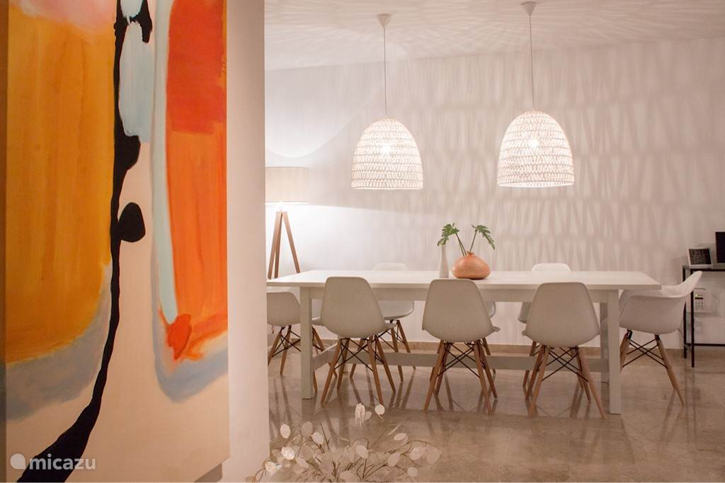 Woonkamer met zicht op eettafel. 3 sets lampen met dimmer, voor een sfeervolle verlichting. De lampen boven tafel geven 's avonds een bijzonder effect op de muren. Schilderijen in huis zijn handgeschilderd door kunstenaars.