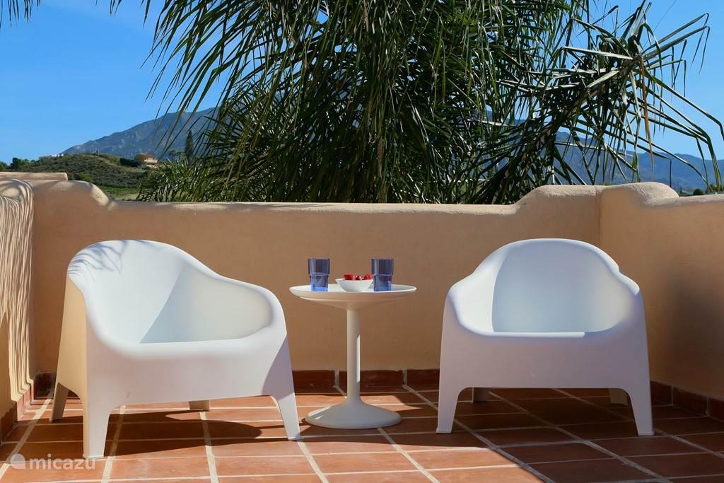 In totaal 4 grote loungestoelen. Een heerlijke plek om te ontbijten of 's avonds de dag af te sluiten. Op de achtergrond La Concha, de berg die zorgt voor het heerlijke microklimaat in Marbella.