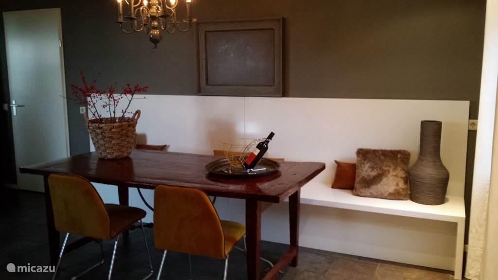 Keukentafel met een lange bank, deze zorgt voor veel ruimte.