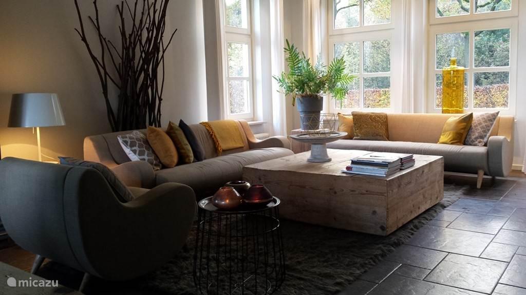 De lichte woonkamer met zithoek