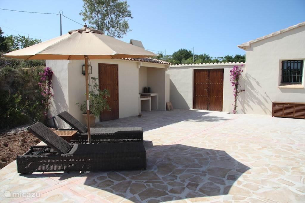 Groot zonnig terras met comfortable ligbedden en grote parasol.