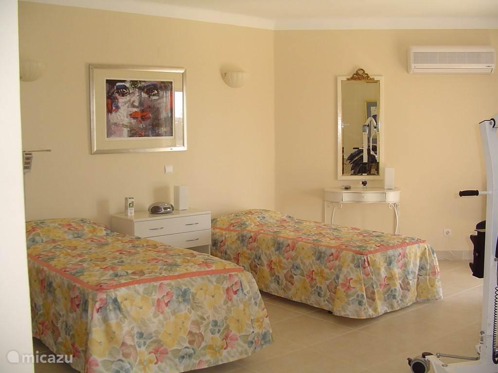 slaapkamer begane grand met aansluitende badkamer. Ruime kleerkast en satelliet TV