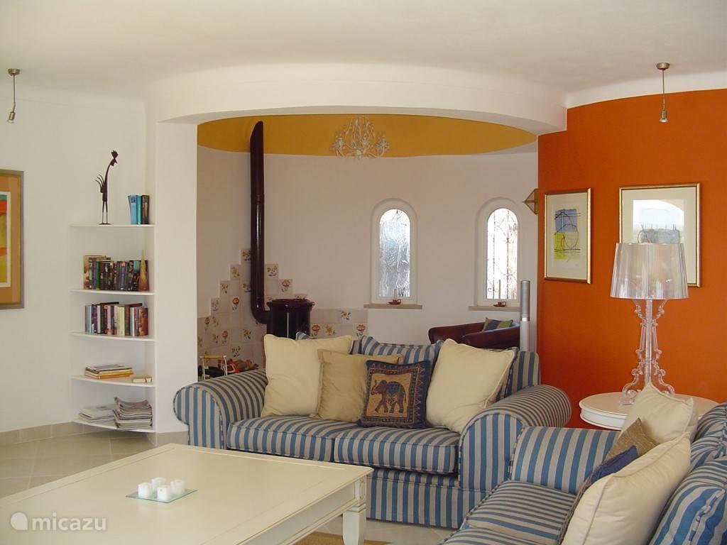 Deel van de woonkamer met leeshoek bij de houtkachel