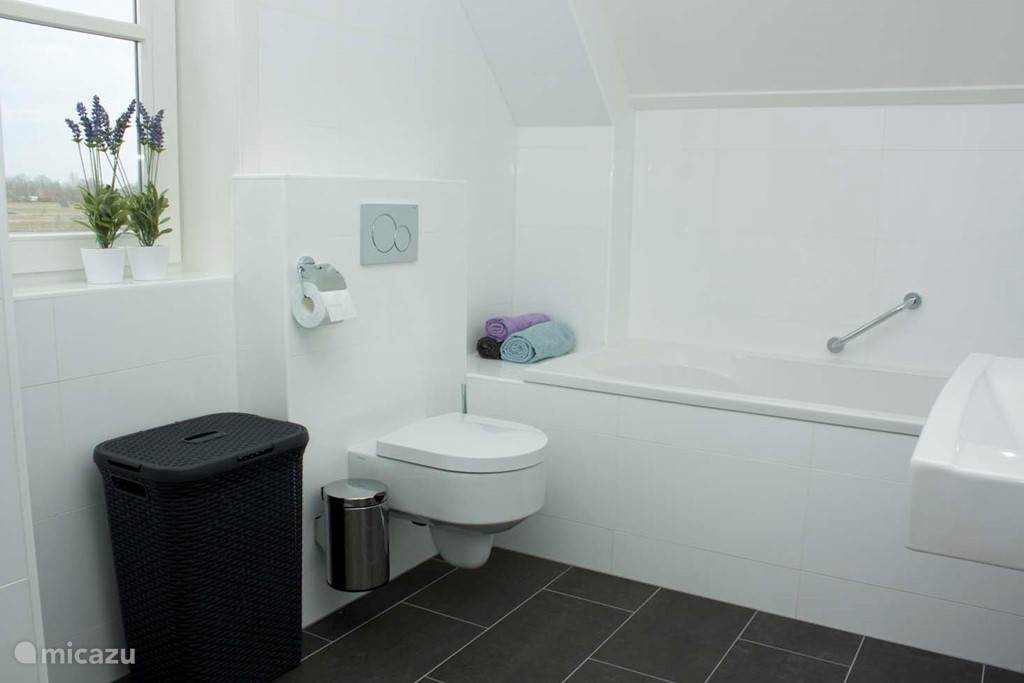 De badkamer ligt op de eerste verdieping en is voorzien van een ligbad, douche, toilet en wastafel.