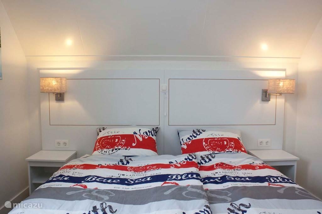 Een van de slaapkamers met 2 boxspringbedden. Alle slaapkamers liggen op de eerste verdieping.