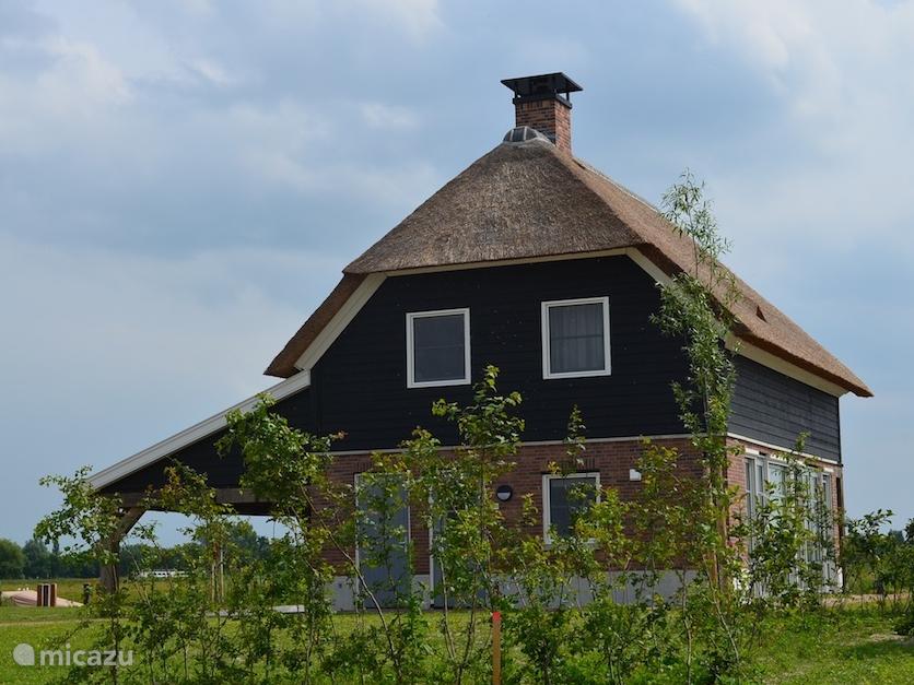 Vakantiewoning Schiphuiswoning 533 op Waterresort Bodelaeke in Giethoorn. Links ziet u het overdekte boothuis. Aan de andere kant van de vakantiewoning ligt het water en terras. Bij deze vakantiewoning kunt u voordelig de luxe sloep van de eigenaar erbij huren.