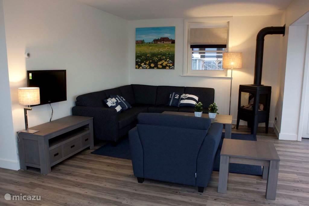De ruime woonkamer heeft een grote raampartij met uitzicht over het water en het natuurgebied. De gashaard zorgt voor veel sfeer in de woonkamer.