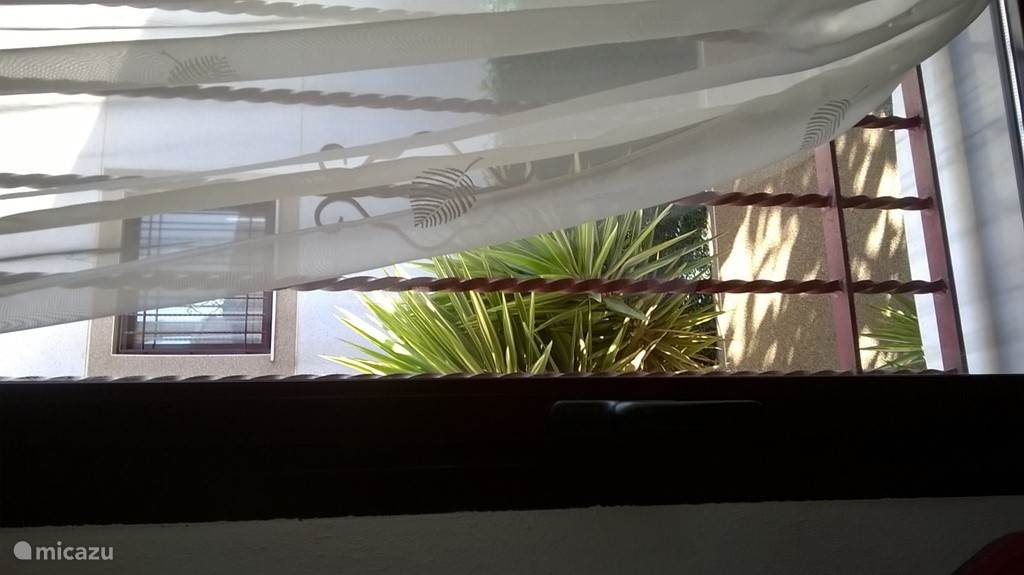 De woonkamer met rondomrond ramen wat voor veel licht zorgt. 's Avonds en 's nachts kunnen de rolluiken naar beneden worden gedaan.