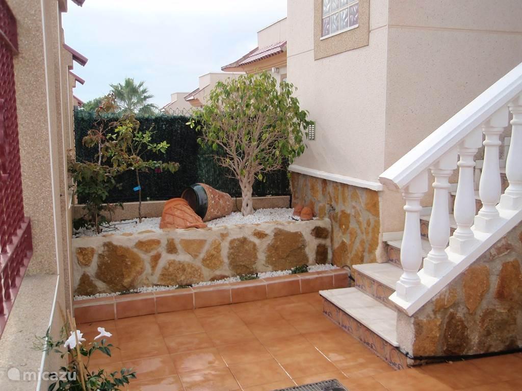 Het overdekt terras is bereikbaar  via enkele trappen en meteen heb je een mooi uitzicht op de straat en de omgeving.