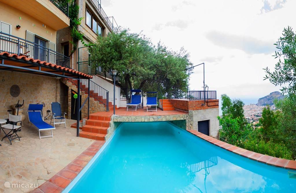 Zwembad. Het appartement L'Alba is midden boven achter de olijfboom, naast de grote ramen.