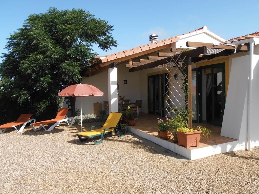 Overdekt terras van bungalow met openslaande deuren van woonkamer en slaapkamer met dubbelbed.
