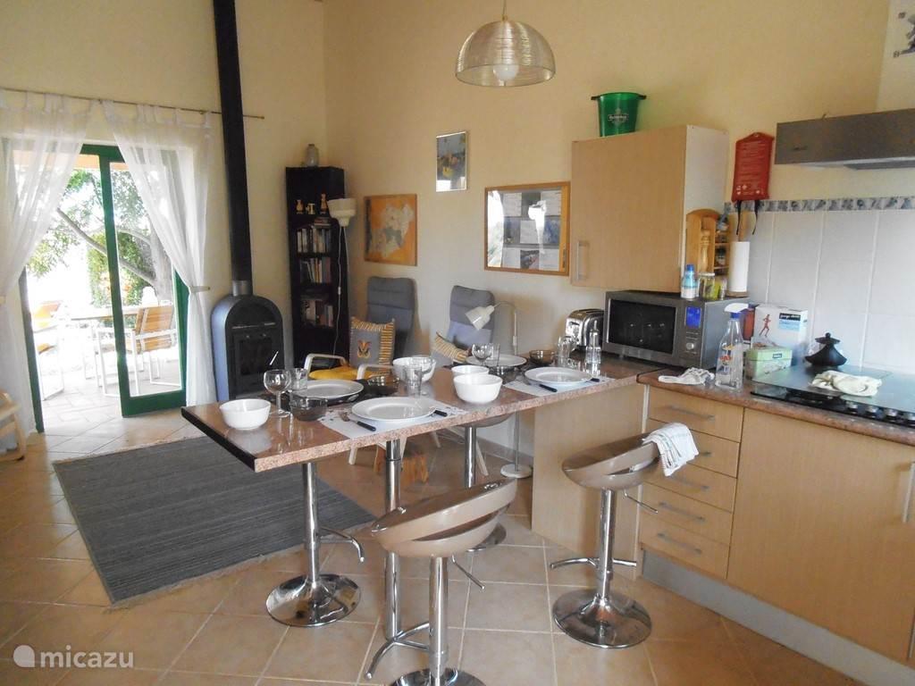 Blik vanaf de ingangsdeur op eetbar en woonkamer met houtkachel