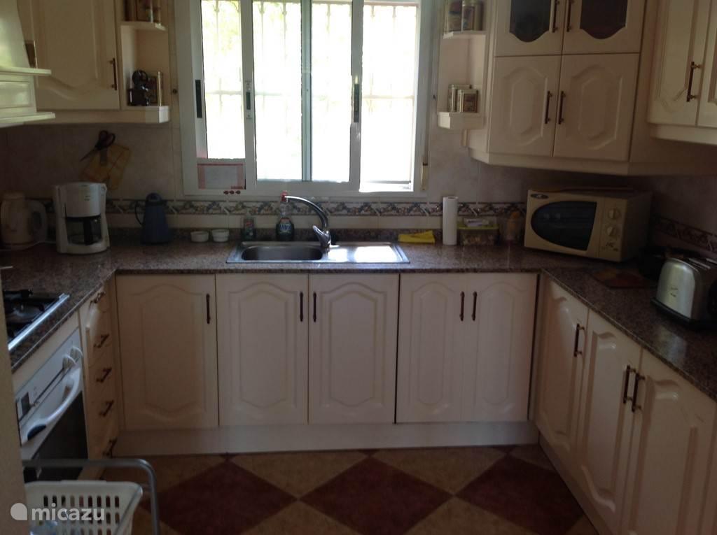 Keuken in U - opstelling met alle apparatuur zoals koel-vriescombinatie, vaatwasmachine, 4 pits gasfornuis, afzuigkap, oven, magnetron.
