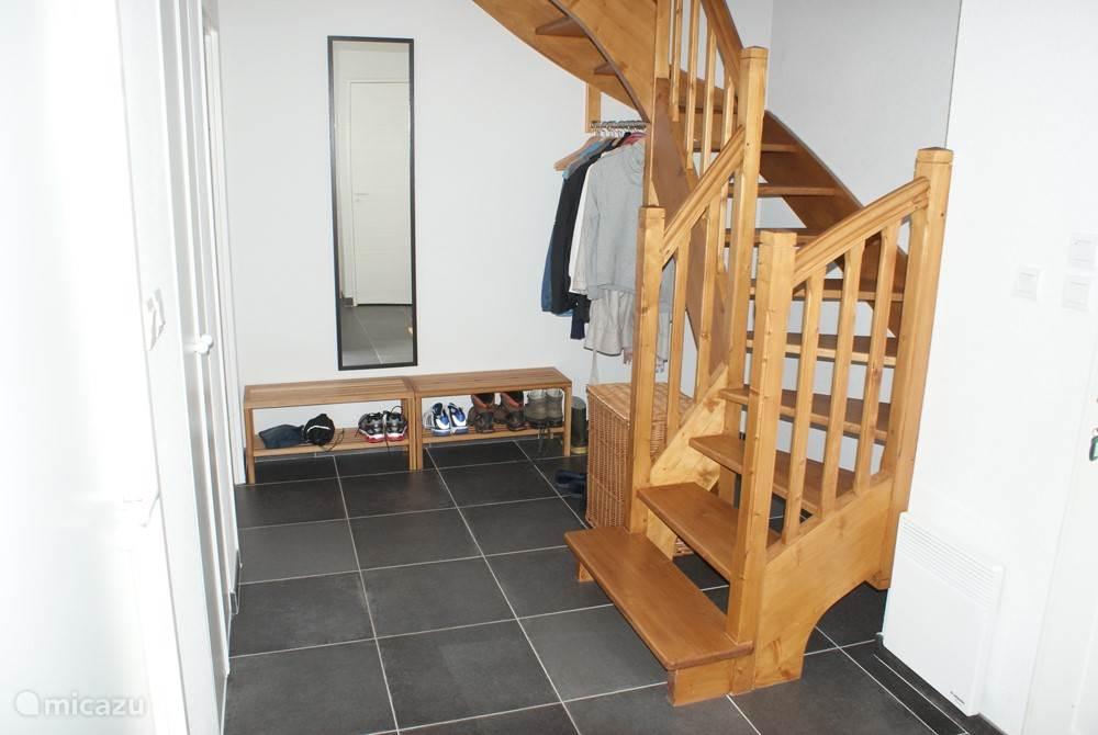 Ruime hal met wc, voorraadkast, garderobe en trap naar 1e verdieping.