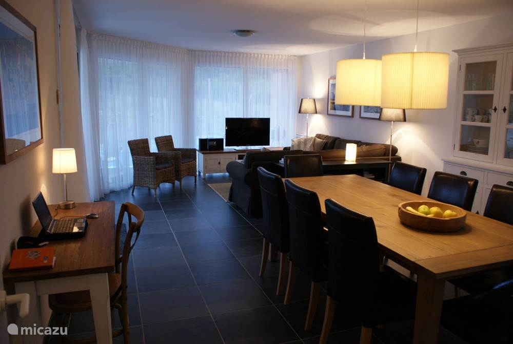 Spacious living room with sofa, dining table for eight people and work table.