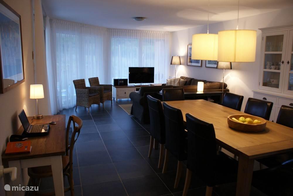 Ruime woonkamer met zithoek, eettafel voor 8 personen en werktafeltje.