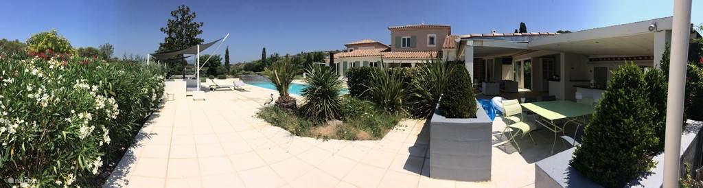 Panoramafoto van de zwembadzijde en het huis