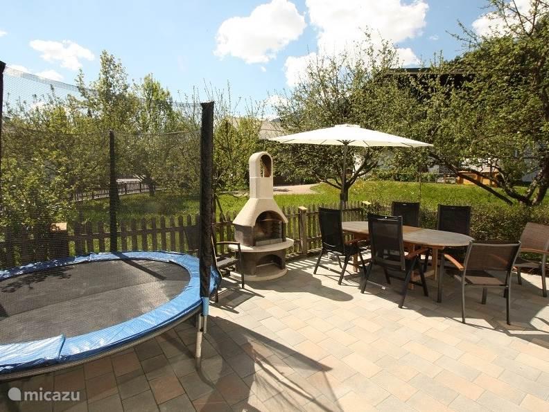 Op het beschutte terras met tuindeurtje staat voor onze kleine gastjes een trampoline