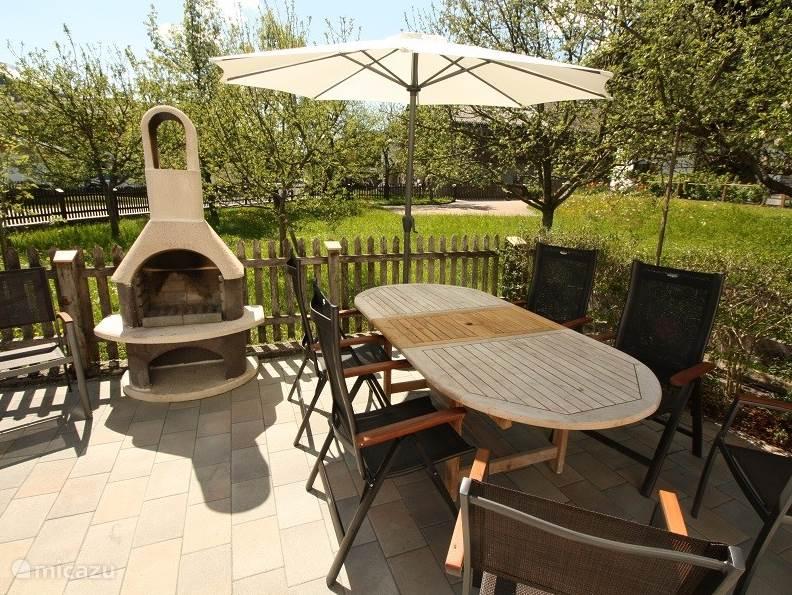 Tuinhaard Grill en comfortabele tuinmeubelen op het zonnig op het Zuid Westen gelegen terras met prachtig uitzicht