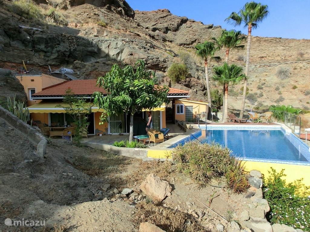 Blik op villa, terras en zwembad
