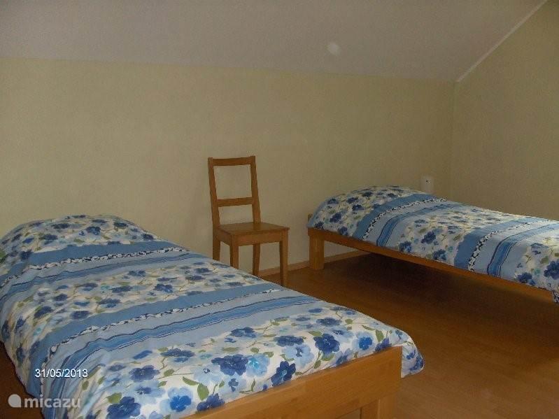 Slaapkamer boven met twee eenpersoonsbedden en kast.
