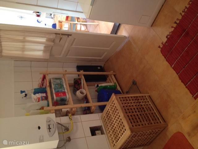 Hoekje van de badkamer met deur naar keuken.