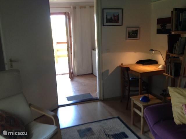 Huiskamer met deur naar hal.