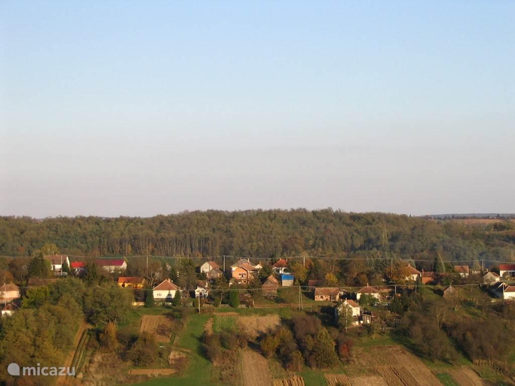 Milejszeg vanaf de heuvelrug aan de overkant. Uitzicht op de vallei. Linksonder op de foto ligt ons huisje tussen de huizen met de vurrode daken en het huisje met het meest witte frontje in. Het is geel en ligt wat verscholen.